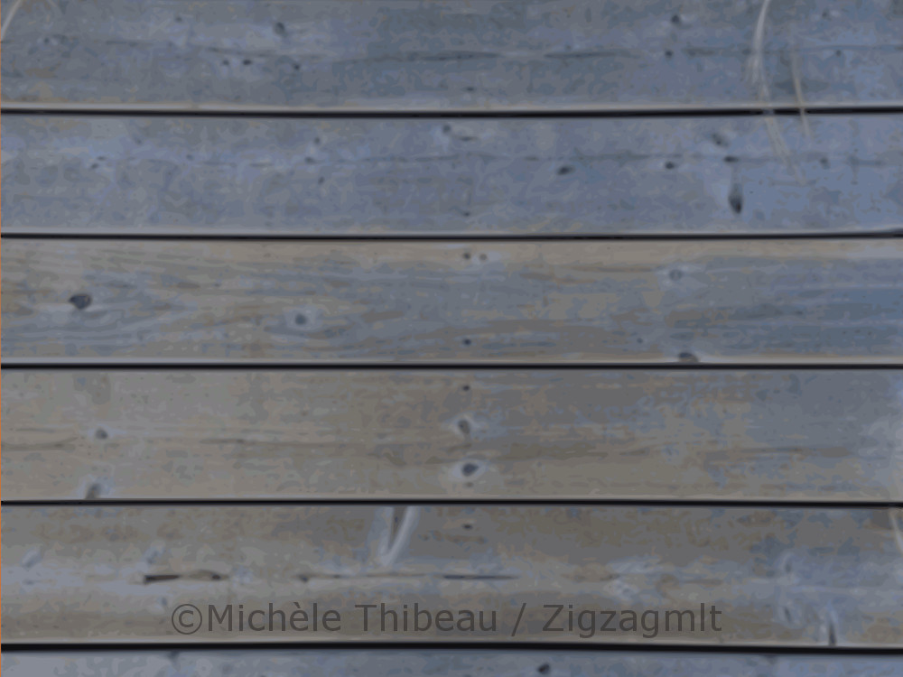The bluish planks of the wharf, the walkway at Paspebiac in the region of Gaspé, captured in the light of evening.